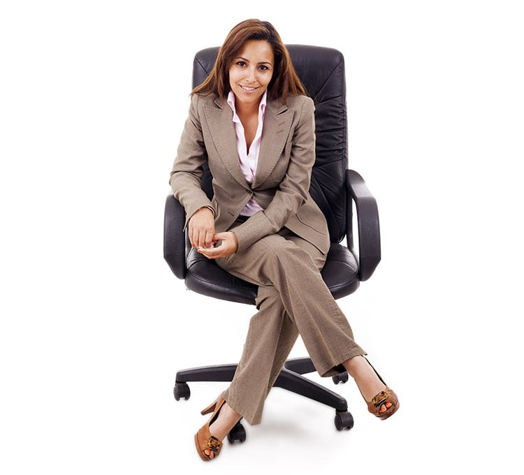 A woman wearing business attire sitting in a chair
